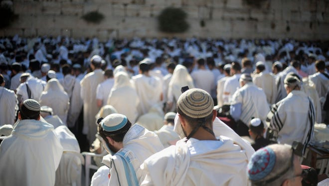 In this May 24, 2017 file photo, Jewish men pray at the Western Wall, the holiest place where Jews can pray, in Jerusalem's Old City.
