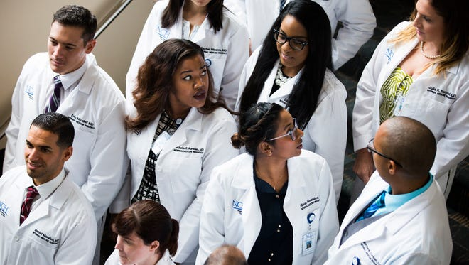 Residents come together for a group photo after the white coat ceremony on Monday, June 26, 2017, at the Telford Center Auditorium at NCH Baker Hospital Downtown.