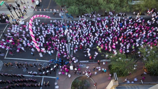 People take off from the starting line for the 1-mile run during the 22nd annual Susan G. Komen Race for the Cure in downtown Phoenix. on Sunday, Oct. 12, 2014.