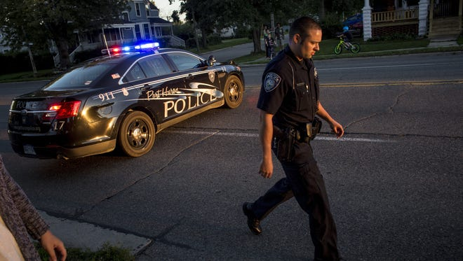 Port Huron Police Officer Derek Paret walks from his patrol car responding to the scene of an accident on Lapeer Avenue in 2016.