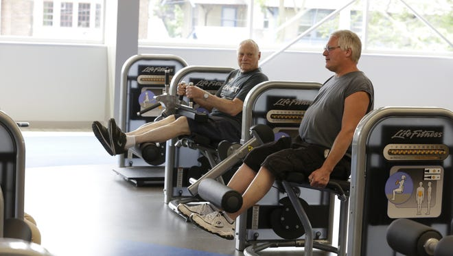 Bruce Salzer used the leg extension machine while his father, John Salzer, uses the leg curl machine Thursday, July 13, 2017, during a tour of the renovated Downtown Oshkosh YMCA.