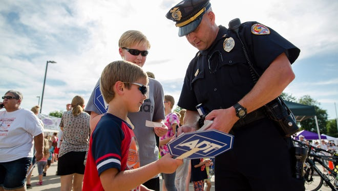 Zachary Harris and Madalyn Harris get autographs from Urbandale Police Captain Matt Logsdon on Aug. 2, 2016, during National Night Out at the Urbandale Police Department.