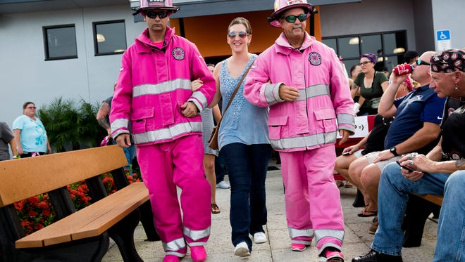 "Nonnie Ivey, who is fighting breast cancer for the third time, is escorted by Pink Heals volunteers Bobby Sarazen, left, and Troy Fullon to the Pink Heals firetruck during the ""Endless Summer Bike Night"" at Naples Harley Davidson Saturday, July 22, 2017. ""It's crazy overwhelming. I'm usually low key,"" Ivey said. ""I truly appreciate everything."" All money donated during the fundraiser went towards Ivey's medical expenses."