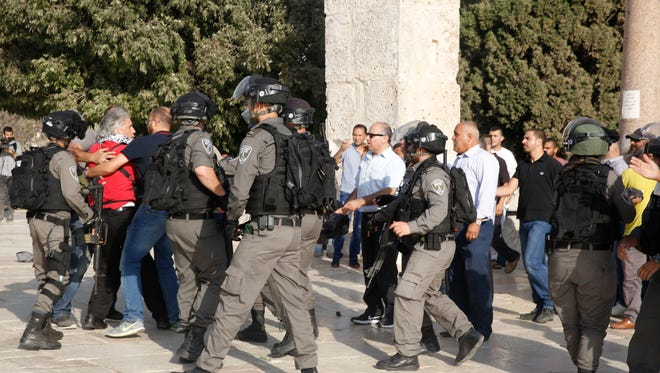 Palestinians and Israeli border police officers scuffle inside the Al Aqsa Mosque compound in Jerusalme on July 27, 2017. Thousands of Muslims flocked to the  shrine for the first organized prayers at the holy site in nearly two weeks.