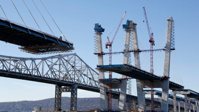 In a Dec. 20, 2016 file photo, a span on the new Tappan Zee Bridge, foreground, awaits completion while motorists continue to use the older bridge, background, near Tarrytown, N.Y. The former governor's son, New York Gov. Andrew Cuomo, on Thursday, June 29, 2017, signed into law a bill naming the new Tappan Zee Bridge the Gov. Mario M. Cuomo Bridge. Mario Cuomo served as governor from 1983 to 1994 and was often mentioned as a possible White House contender.