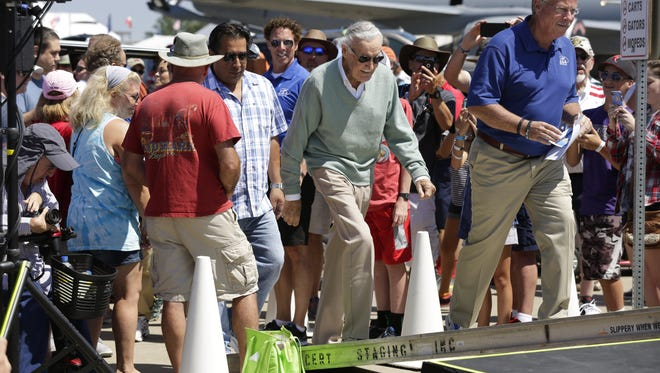 Comic book legend Stan Lee, center, walks onto a stage Friday at EAA AirVenture's Boeing Plaza with Jack Pelton, CEO of EAA.