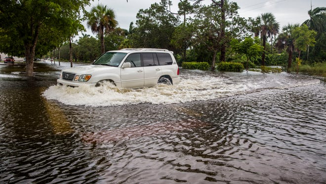 Cars drive through a flooded 11th Street North in River Park on Friday, Aug. 25, 2017.