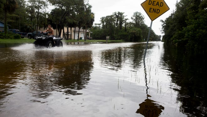 Kayden Cecil drives along Hickory Wood Drive as steady rains flooded many side roads and driveways off of Logan Boulevard August 27, 2017 in Naples.