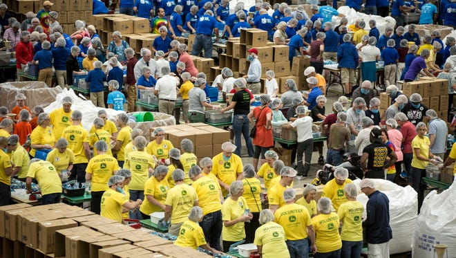 Volunteers prepare packaged meals, Thursday, Aug. 31, 2017, at the Iowa Events Center in Des Moines, Iowa. The Tenth Annual Hunger Fight has a goal of packaging 5 million meals this weekend to reach a milestone of 100 million total meals.