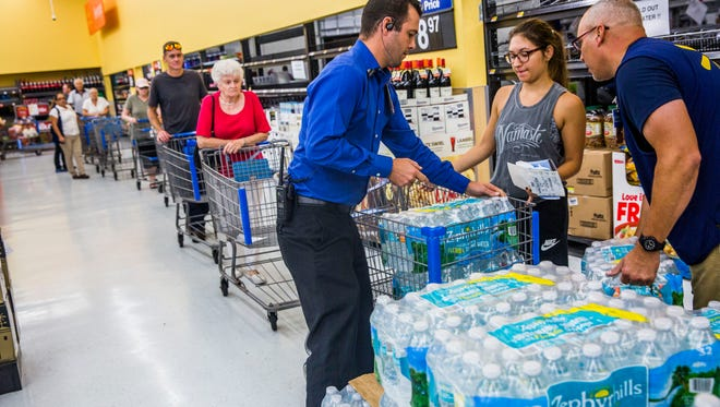 People line up for cases of water at Walmart on Immokalee Road on Wednesday, Sept. 6, 2017 in preparation for Hurricane Irma.