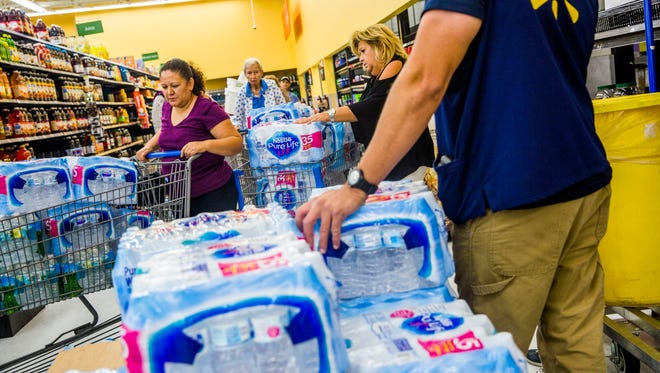 People line up for cases of water at Walmart on Immokalee Road on Sept. 6, 2017, in preparation for Hurricane Irma. The Bureau of Emergency Services suggests a minimum of 4 gallons of water per person and pet, per day, for a minimum of 14 days.