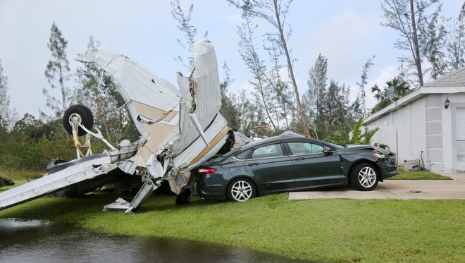 A plane from Buckingham Field sits atop a car  on Sunset Rd. in Lehigh a day after Hurricane Irma moved through Lee County.