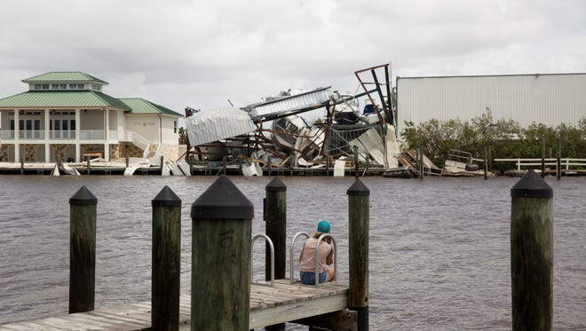 A woman looks across the channel to a demolished marina in Goodland, Fla. Monday, September 11, 2017.