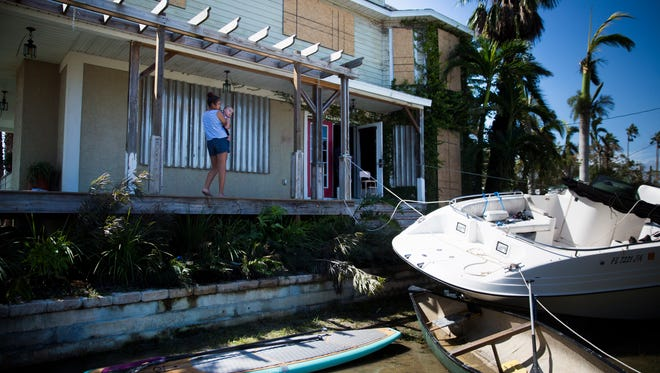 Addy Valdez, 12, holds her cousin, Jasmine, while her family starts to clean up the damage from Hurricane Irma on Monday, September 11, 2017 on Copeland Avenue in Everglades City.