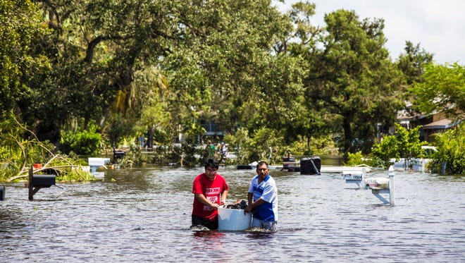 Paulino Ortiz, 46, and his son carry a barrel of belongings from their house through floodwater from Hurricane Irma in Bonita Springs on Monday, Sept. 11, 2017.