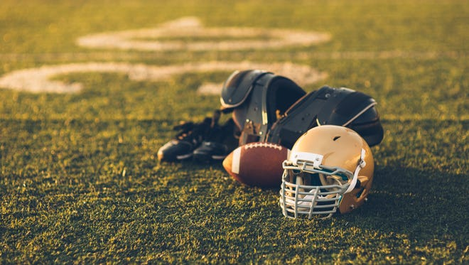 A football helmet sits with a football on a football playing field.