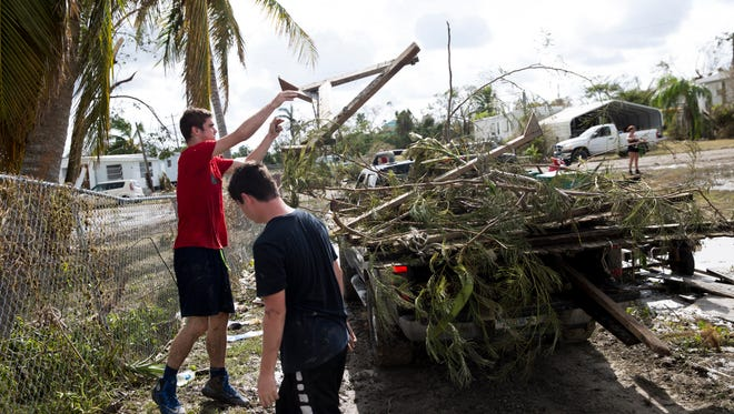Kalen Kivodeaux, 16, left, and his brother Ivan, 13, clear debris from outside their grandmother Lisa Daniels front yard as residents begin to assess and repair damage from Hurricane Irma to their homes Tuesday, September 12, 2017 in the small island community of Chokoloskee, Fla. just south of Everglades City.