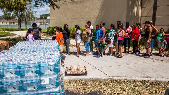 People wait in line for food and water from Collier County and Meals of Hope outside of Immokalee High School on Wednesday, Sept. 13, 2017.