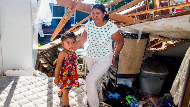 Eustolia Flores and her daughter Jocelyn, 1, stand in their trailer that was destroyed by Hurricane Irma in Immokalee on Wednesday, Sept. 13, 2017. Flores and her four children are staying in their neighbor's trailer with them for now.