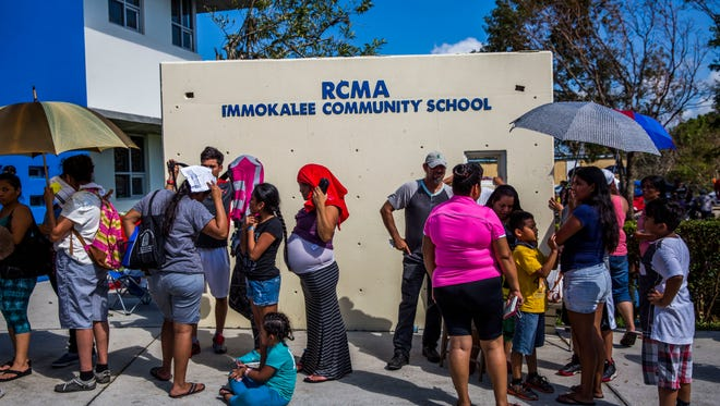 People wait in a line wrapped around the Redlands Christian Migrant Association building for FEMA registration assistance in Immokalee on Friday, Sept. 15, 2017.