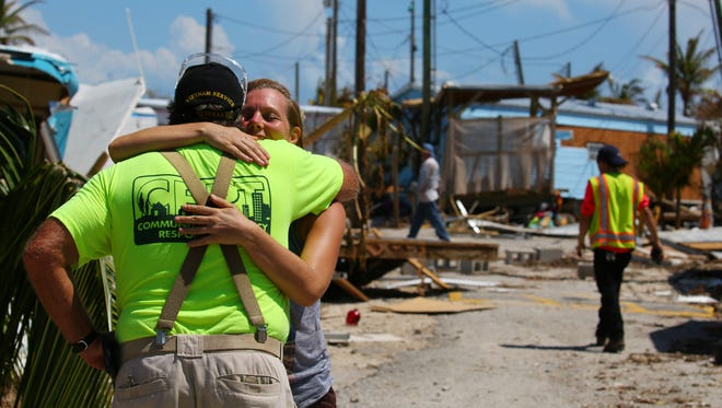 Stephanie Matejcik gets a hug from one of her neighbors as she moves her belongings out of her home at the Sea Breeze Resort in Islamorada, Florida, after Hurricane Irma brought high winds and flooding to the area destroying most of the homes in the community.