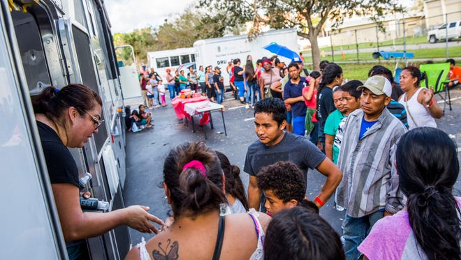 Families wait for donated supplies to be handed out at Immokalee High School on Saturday, Sept. 16, 2017. Kelly Olsen's family drove a trailer full of donations to Immokalee from Minnesota.