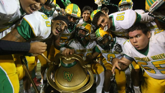 The Coachella Valley football team celebrates around the Victory Bell after beating Indio for the sixth game in a row Friday night.