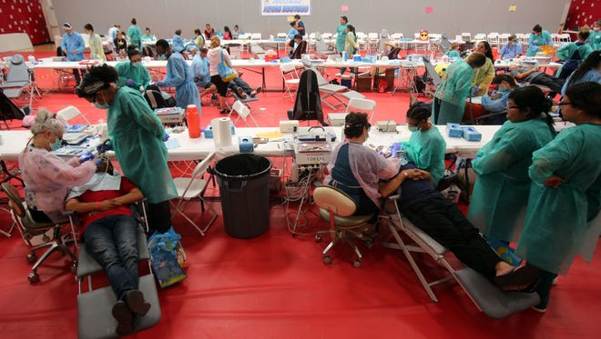 Dental professionals work with patients inside the Desert Mirage High School gym on Saturday, September 16, 2017 during the Flying Doctors health fair in Thermal.