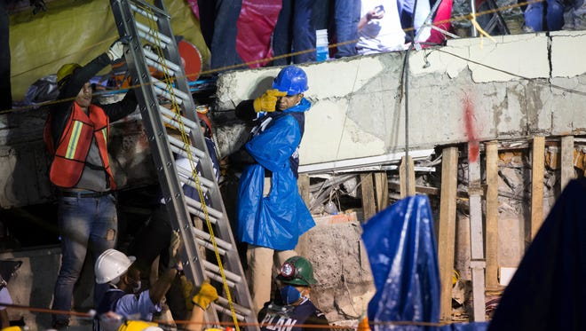 A ladder is raised to search and rescue team members during rescue efforts at the Enrique Rebsamen school in Mexico City, Mexico, on Sept. 21, 2017.