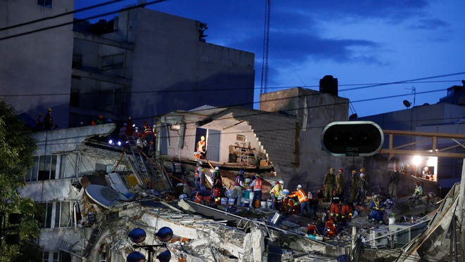 Rescuers race to save people believed to be still alive inside a collapsed office building in the Roma Norte neighborhood of Mexico City, as night falls Friday, Sept. 22, 2017, three days after a 7.1 magnitude earthquake. Hope mixed with fear Friday in Mexico City, where families huddled under tarps and donated blankets, awaiting word of their loved ones trapped in rubble.