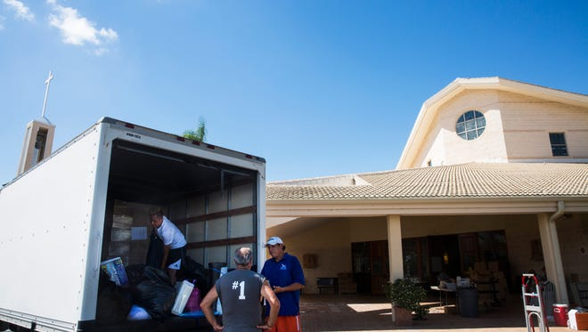 Volunteers load a truck with supplies at Saint John the Evangelist Catholic Church in North Naples on Saturday, Sept. 23, 2017.