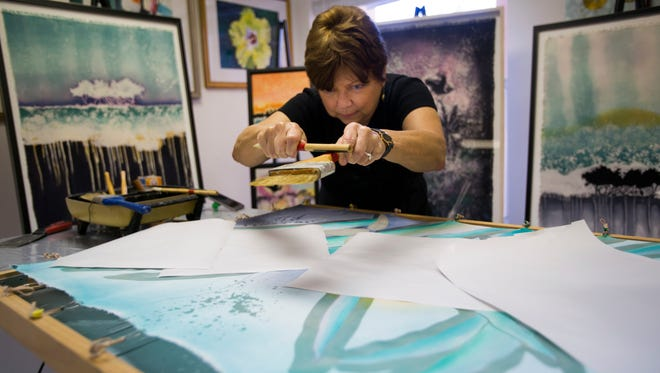 "Leigh Herndon shakes a brush with hot wax to create a ""wax snowstorm"" on her fabric on Thursday, September 7, 2017 at her studio in the art district in North Naples. Herndon uses a Japanese art form called Rozome which is a wax-resist fabric dyeing technique."