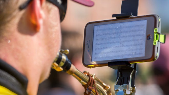"""The Marching Chiefs are using the """"eFlip"""" attachment which allows them to use smart phones instead of printed music."""