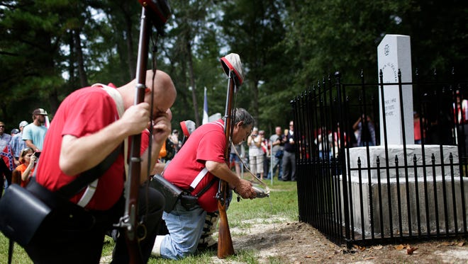 "FILE- In this Aug. 27, 2017 file photo members of the Sons of Confederate Veterans kneel in front of a new monument called the ""Unknown Alabama Confederate Soldiers"" in the Confederate Veterans Memorial Park in Brantley, Ala. As Confederate statues across the nation get removed, covered up or vandalized, some brand new ones are being built as well."