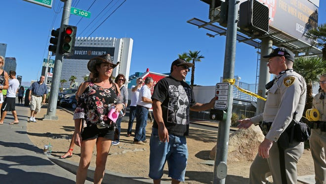 A police officer speaks to people on the Las Vegas Strip Monday, Oct. 2, 2017, in Las Vegas. A mass shooting occurred late night Sunday at a music festival on the Las Vegas Strip. (AP Photo/Ronda Churchill)