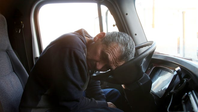 Reyes Castellanos, 58, has gallstones and no health insurance, because he is labeled an independent contractor instead of an employee. Near-constant pain causes him to wince repeatedly as he talks from the cab of his truck.