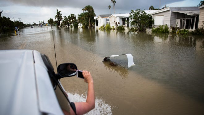 Olga Schramm uses her phone to record a video of flooding as she enters Everglades City in an attempt to return home to Chokoloskee on Sept. 11, 2017, a day after Hurricane Irma struck Southwest Florida. Katie Klann/Naples Daily News
