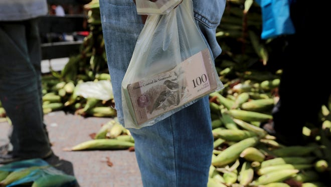 A vendor holds bank notes in a plastic bag Sept. 23 at a market in Caracas, Venezuela. Venezuelans already struggling to find food, medicine and other basic necessities have a new headache to worry about: shortages of cash.