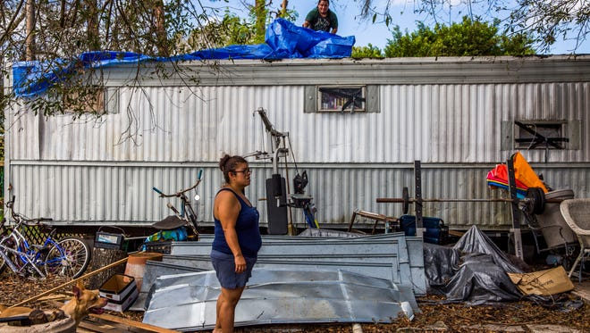 Samantha Tindell stands outside her damaged Immokalee trailer as her partner Antonio Martin puts a tarp over the roof on Saturday, Sept. 23, 2017. Despite the fact that part of their trailer's ceiling is collapsing and there is mold in one the rooms, FEMA said they are ineligible for housing assistance, because Hurricane Irma didn't make their home unsafe to continue living in.