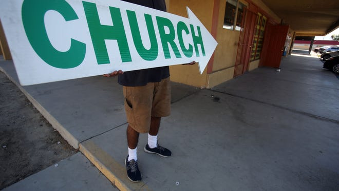 A sign spinner for the Oklevueha Native American Church located in a strip mall off Harrison Blvd in Coachella on Tuesday, October 17, 2017.