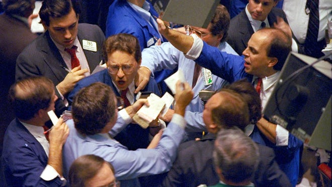 FILE - In this Oct. 19, 1987, file photo, traders work on the floor of the New York Stock Exchange, the day the Dow Jones industrial average fell more than 22%, its biggest one-day plunge ever.