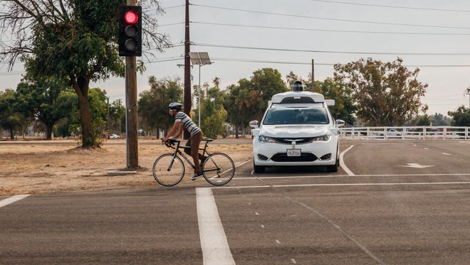 A Waymo self driving minivan stops for a cyclist at the company's private test facility in central California.