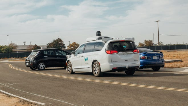 A Waymo minivan outfitted with self-driving sensors brakes suddenly for a black car that has backed out of a driveway without looking. The test was conducted at Waymo's testing facility in central California.