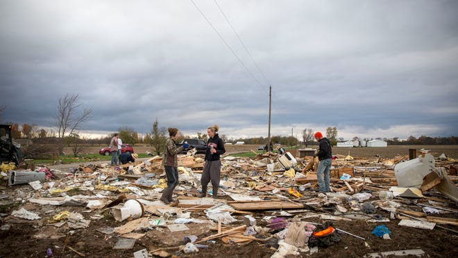 Family, friends and neighbors help clean up what remains of the Walter's family home on along North 500 West near Portland on Nov. 6 after a tornado ripped through the area. The national weather service confirmed a large tornado had impacted the area, but did not have other details as of yet.