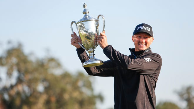 Mackenzie Hughes celebrates with the trophy after winning the RSM Classic at Sea Island Golf Club - Seaside Course on Nov. 21, 2016.