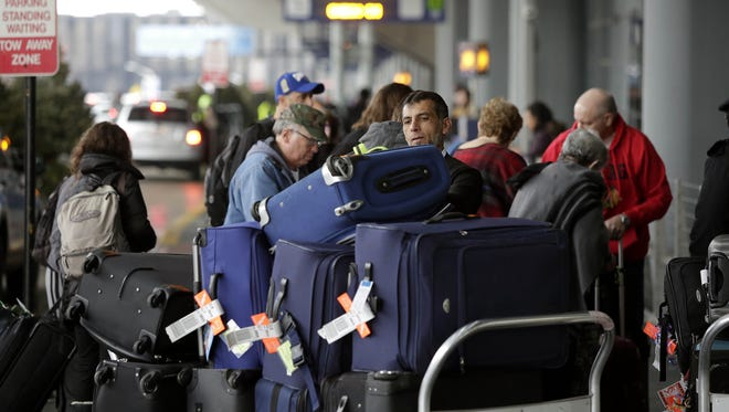 An airport worker organizes luggage on a cart as travelers in the back ground and in the pre check-in line at O'Hare International Airport on Dec. 23, 2016, in Chicago.