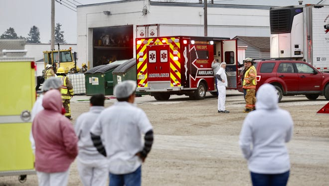 Light smoke comes out of Knaus Cheese, in Rosendale, as workers look on Friday morning. Multiple fire departments were called to extinguish a blaze caused by a reported explosion. At least one person was injured and were transported by ThedaStar.