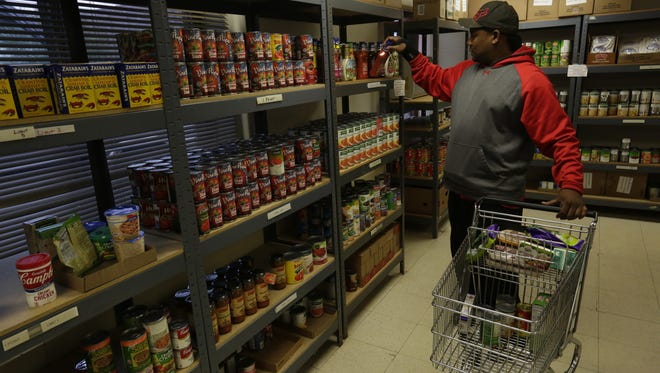 A volunteer stocks shelves at the Salvation Army Food Pantry.