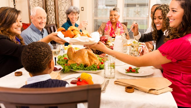 Family and neighbors gather together for Thanksgiving dinner.