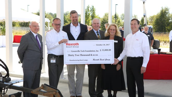 Les Gardner (far left), Dr. Keith Miller (third from right) and Ann Wright (second from right) of Greenville Technical College receive a check from Christoph Kleu (second from left), Claude Bray (third from left), and Mike McCormick (far Right) of Bosch Rexroth. The money will be used to establish the Advanced Manufacturing Academy for high school seniors.